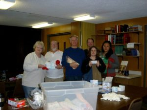 Our Global Mission Committee offers the congregation unique ways of supporting charitable causes both on a local and world-wide basis through creative special offering opportunities. Various items from gently used children's books to bath size bars of soap have been collected and sent to those in need. The picture below was taken as volunteers put together mid-wife kits to aid a global cause. Items for the kits were donated by Pilgrim members.